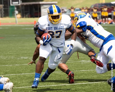 Germaine Tait, FVSU football player, heads down field with ball.