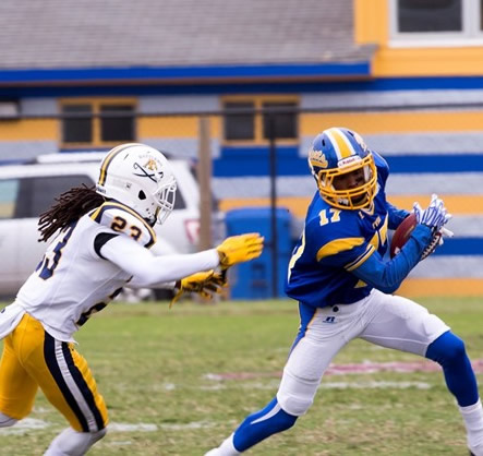 FVSU football player on the field avoids tackle.