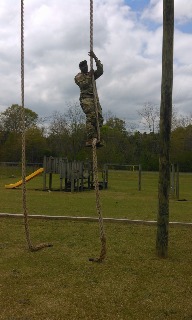 ROTC student climbs to tope of the rope in field.