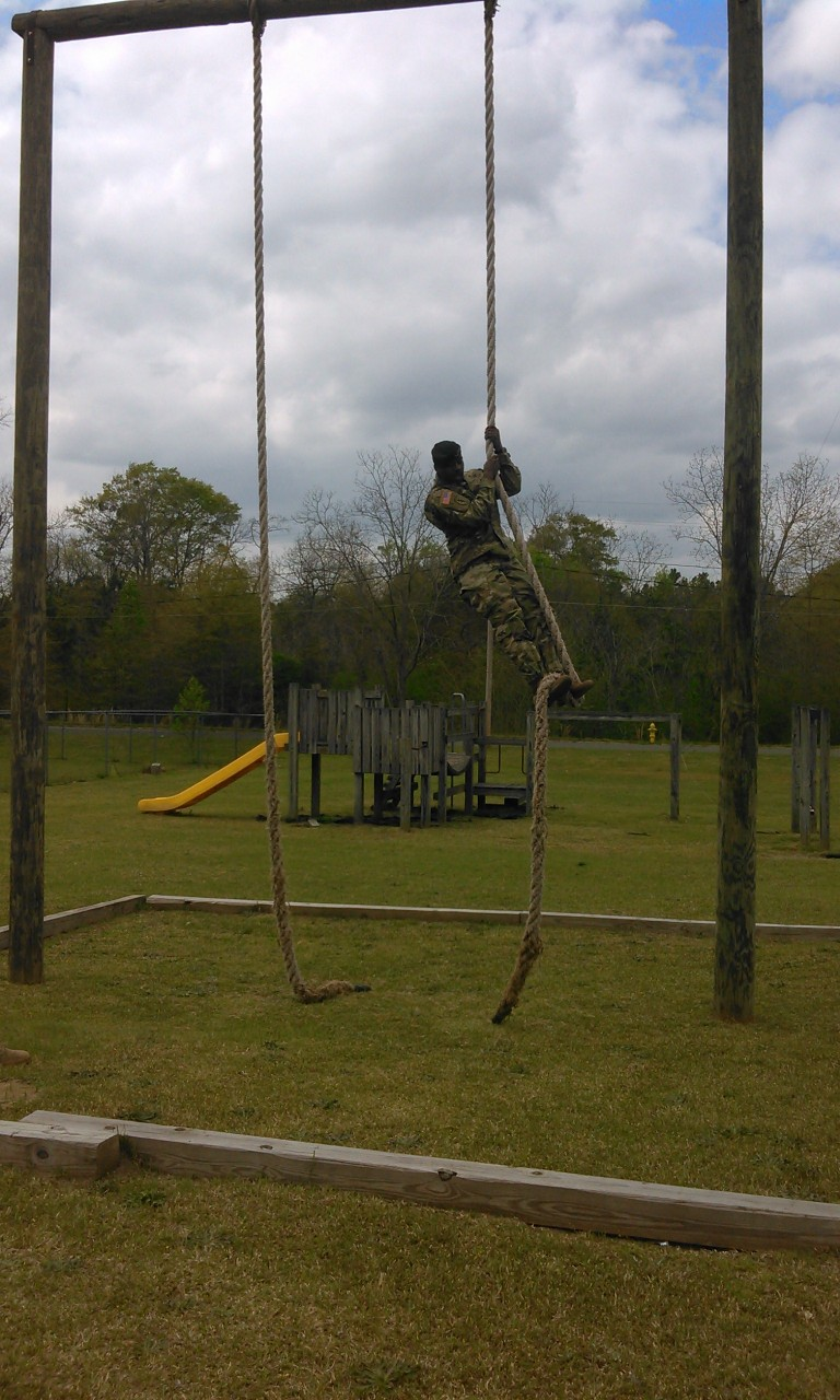 ROTC student climbs to top of rope.
