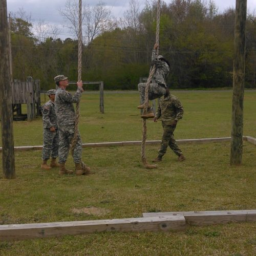 ROTC students in rope climbing exercise.