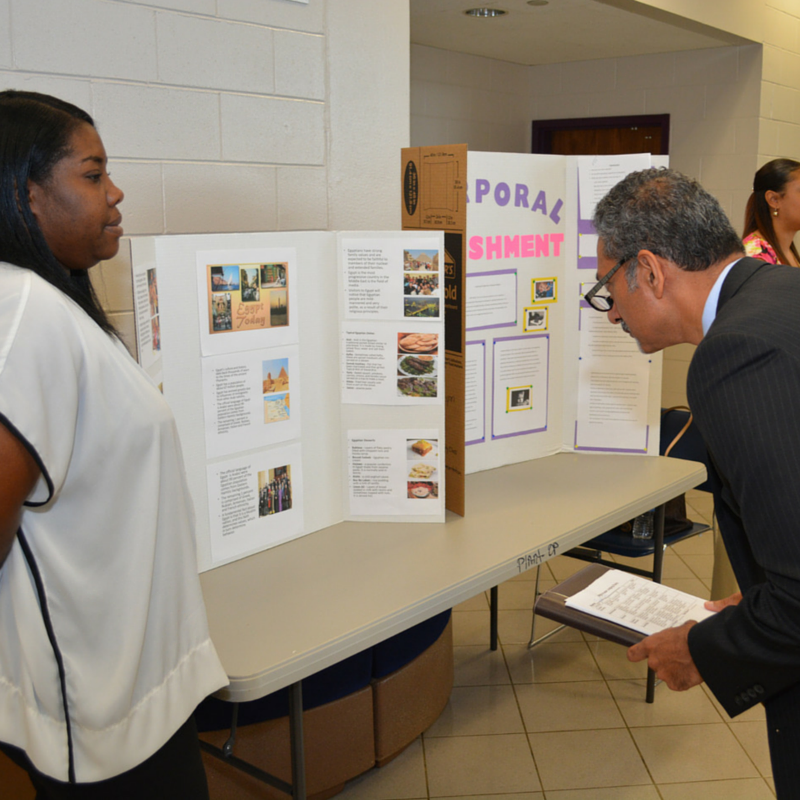 Dr. Uppinder Mehan (right) reads a student's poster presentation during the Banks Pierro Rutland Bellamy Colloquium research competition.